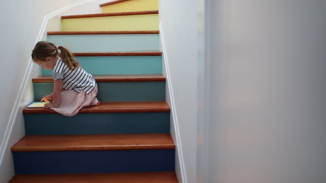 a young girl using a tablet device on a colorful stairway. - piedi nudi bambine video stock e b–roll