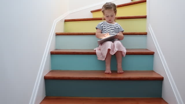 A young girl using a tablet device on a colorful stairway.