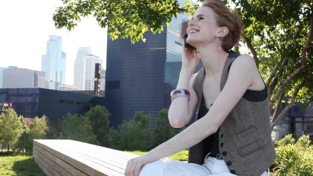 MS Young girl using cellular device outside in urban park smiling and having fun / Minneapolis, Minnesota, United States