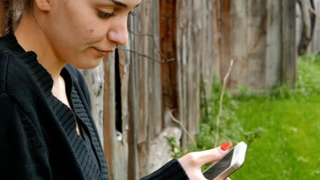 Giovane ragazza, utilizzando il suo smartphone all'aperto