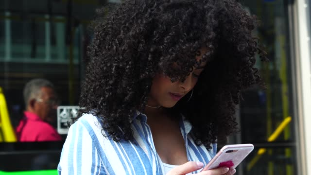 young girl using mobile outdoors - curly stock videos & royalty-free footage