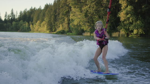 Young girl wake surfing behind boat