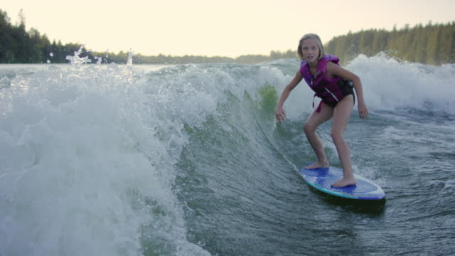 young girl wake surfing behind boat - wakeboarding stock videos and b-roll footage