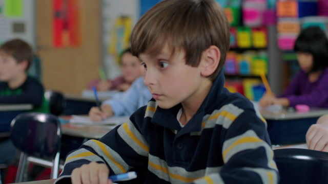 a young girl wakes up her sleeping classmate during a lesson. - aula video stock e b–roll