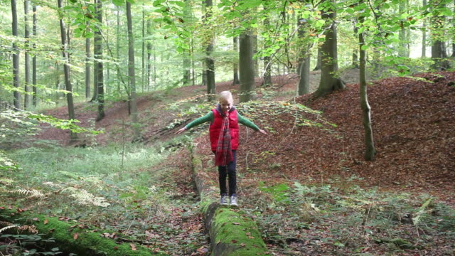 young girl walking along fallen tree in the forest