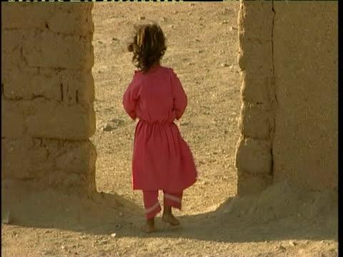young girl walking through archway, desert landscape, afghanistan - endast flickor bildbanksvideor och videomaterial från bakom kulisserna