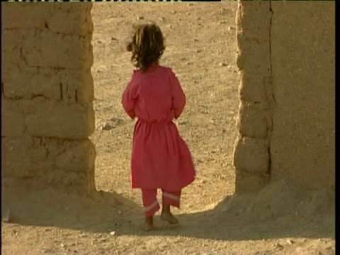 stockvideo's en b-roll-footage met young girl walking through archway, desert landscape, afghanistan - alleen meisjes