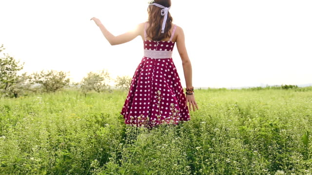 young girl walking through the flowers in a summer meadow - polka dot stock videos and b-roll footage