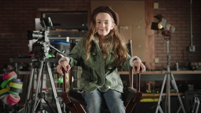 slo mo. young girl walks into frame, climbs into movie director's chair, and smiles at camera on a film set with all female filmmakers. - heimwerken stock-videos und b-roll-filmmaterial