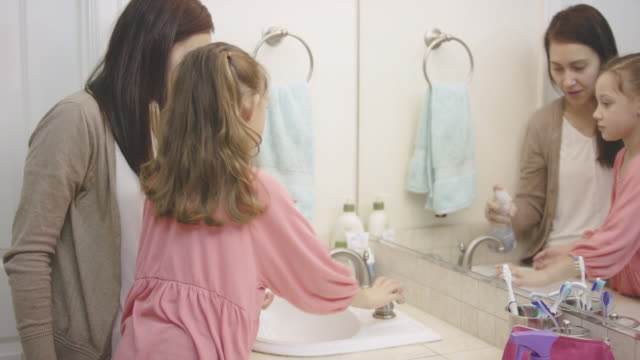 young girl washing hands with her mother in the bathroom - pacific islander child stock videos & royalty-free footage