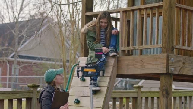 a young girl watches camera monitor from wooden playhouse as female filmmakers shoot a movie in her backyard - skådespelerska bildbanksvideor och videomaterial från bakom kulisserna