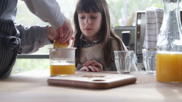 young girl watches mum make orange juice at home - juice extractor stock videos & royalty-free footage