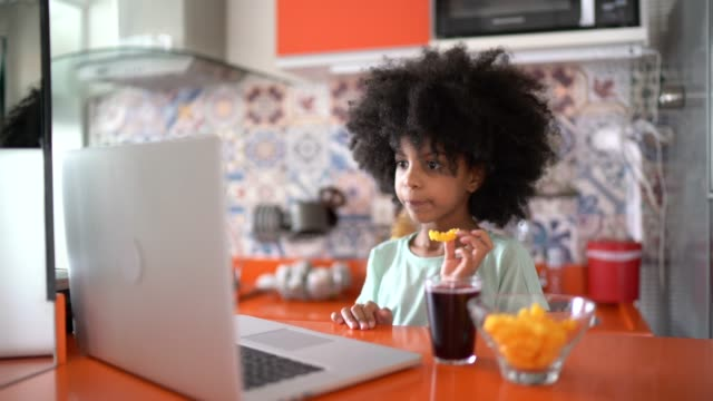 young girl watching movie at home on laptop and eating junk food - pianale da cucina video stock e b–roll