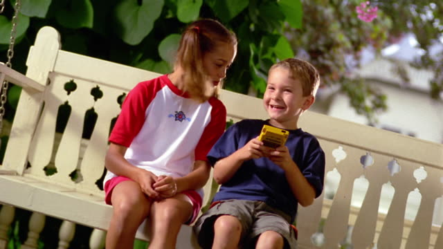 canted ms young girl watching young boy play handheld video game on porch swing - handheld video game stock videos & royalty-free footage