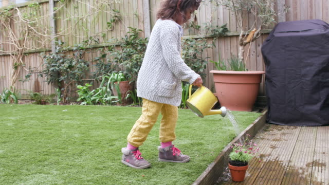young girl watering a flower in her garden - watering can stock videos & royalty-free footage