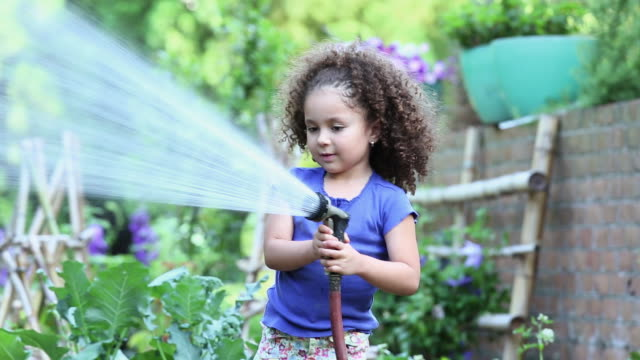 MS DS Young Girl Watering Plants in Home Vegetable Garden / Richmond, Virginia, USA