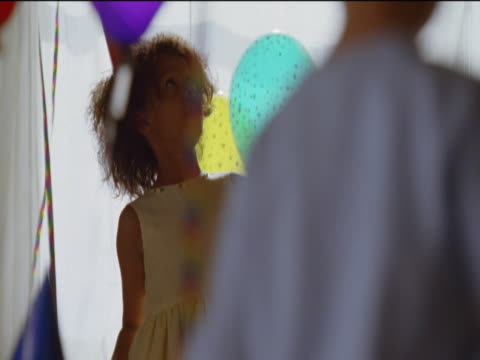 young girl wearing a dress and party hat plays with multi-coloured balloons at a birthday party - party hat stock videos & royalty-free footage