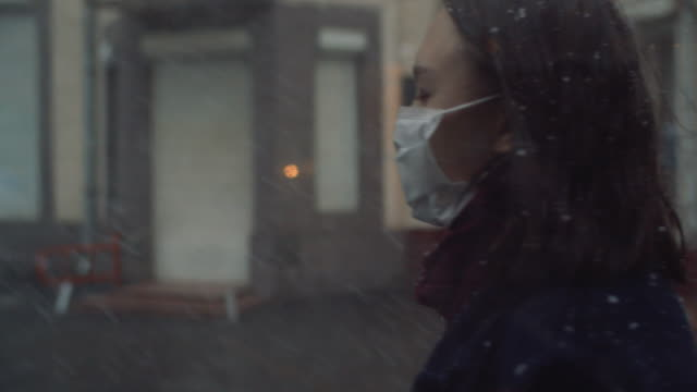 junges mädchen trägt eine schützende gesichtsmaske in der stadt - mundschutz stock-videos und b-roll-filmmaterial
