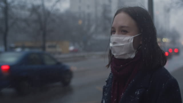 young girl wearing a protective face mask in the city - weather stock videos & royalty-free footage