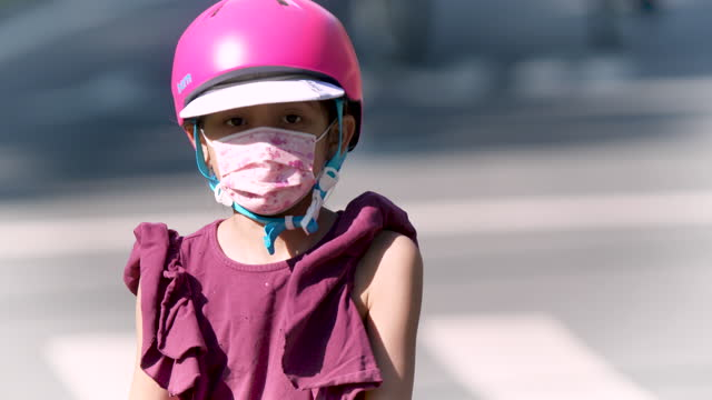 young girl wearing a protective face mask rides a scooter despite the advice to stay home from new york state health officials to prevent the spread... - children only stock videos & royalty-free footage