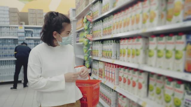 stockvideo's en b-roll-footage met jong meisje dat een beschermend gezichtsmasker draagt dat in supermarkt winkelt. - vermijden