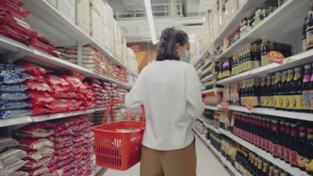 young girl wearing a protective face mask shopping in supermarket. - toxic substance stock videos & royalty-free footage