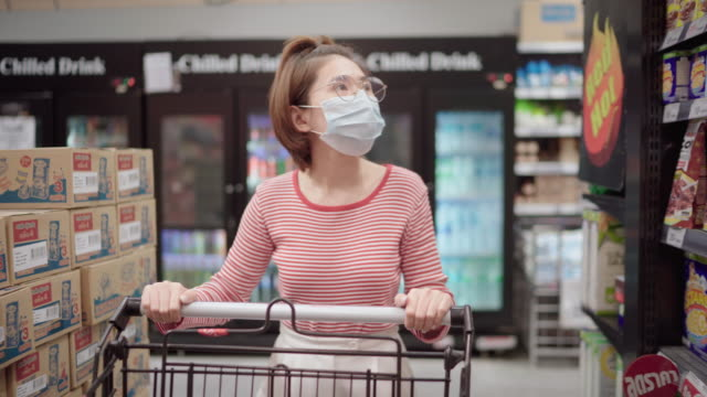 young girl wearing a protective face mask shopping in supermarket - wet wipe stock videos & royalty-free footage