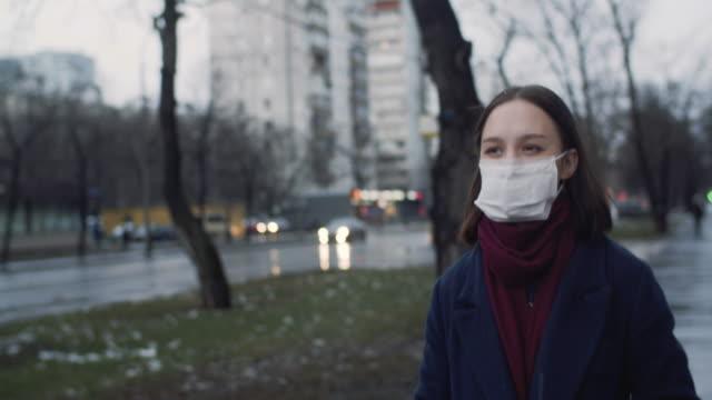 vídeos de stock e filmes b-roll de young girl wearing a protective face mask - vestuário para proteção