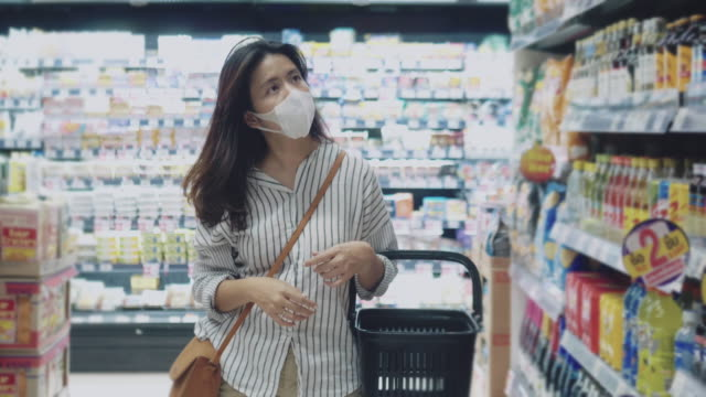 vídeos de stock, filmes e b-roll de jovem usando uma máscara facial protetora - máscara cirúrgica