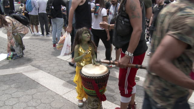 A young girl wearing green body paint plays the Bongos at the Cannabis Day Rally in Union Square Park New York The rally is in favor of the...