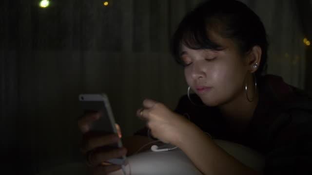寝室でヘッドフォンを着た少女。 - 寝室点の映像素材/bロール