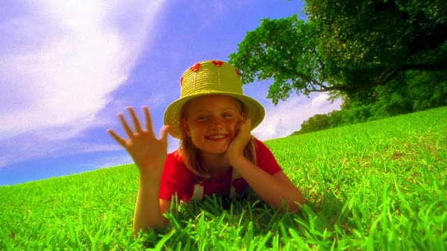 canted ms young girl wearing straw hat lying on grass + waving / florida - straw hat stock videos & royalty-free footage