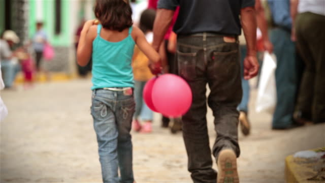 young girl with balloons holds hands with father while walking up crowded cobblestone street - latin america stock videos & royalty-free footage