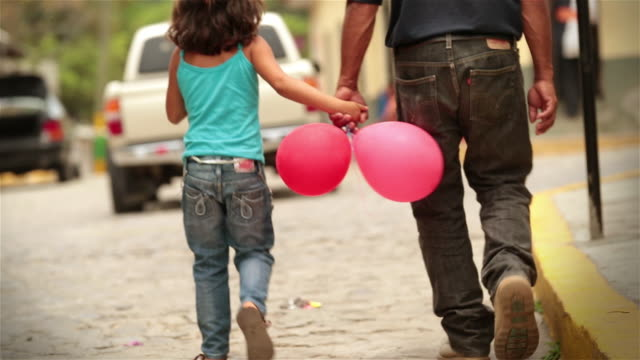 vídeos y material grabado en eventos de stock de young girl with balloons holds hands with father while walking up cobblestone street, turns to look at camera - américa central