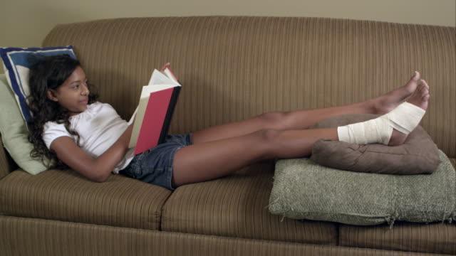 young girl with bandaged knee reading. - 包帯点の映像素材/bロール