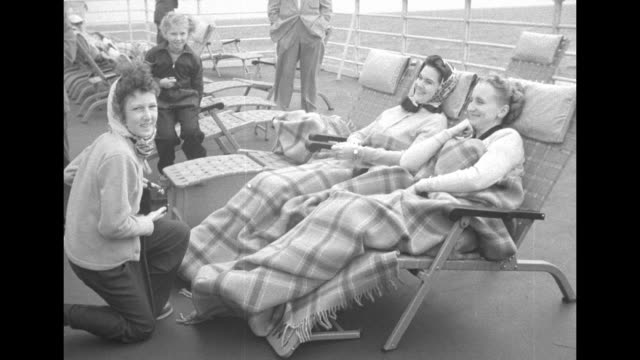 stockvideo's en b-roll-footage met young girl with brownie camera taking pictures / vs margaret truman wrapped in blanket on deck chair poses for photographs on the ss united states /... - margaret truman