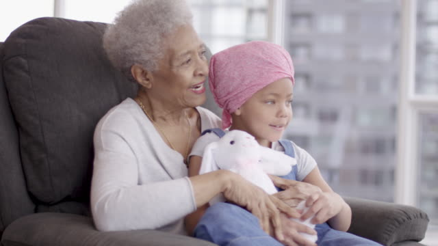 Young girl with cancer hugs grandmother lovingly