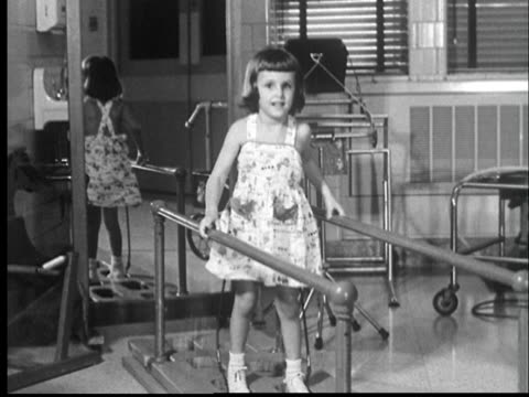 vídeos de stock, filmes e b-roll de 1959 ws young girl with cerebral palsy holding on to hand rails while struggling to walk/ cu girl's face - brace