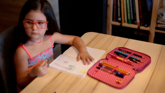Young girl with eyeglasses coloring her drawing