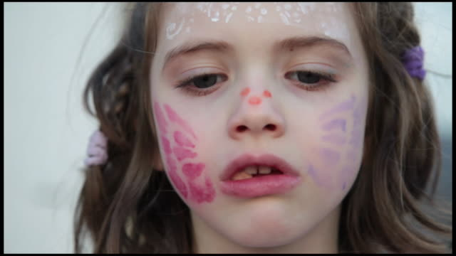 young girl with face painted eating candy, close up, france - gomma da masticare video stock e b–roll