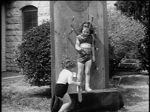 b/w 1955 young girl with knives around her on board gestures to smaller girl to take her place - yorkville illinois stock videos & royalty-free footage