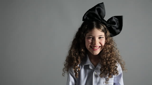 young girl with large black bow in hair - gray background stock videos & royalty-free footage