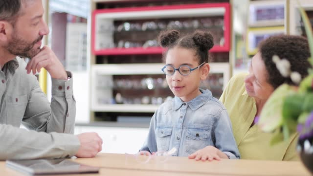 stockvideo's en b-roll-footage met young girl with new glasses at the opticians - oogmeetkunde