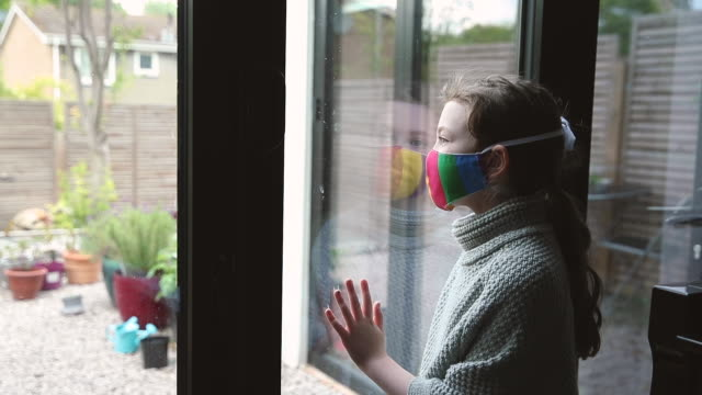 young girl with rainbow mask looking through window - protection stock videos & royalty-free footage