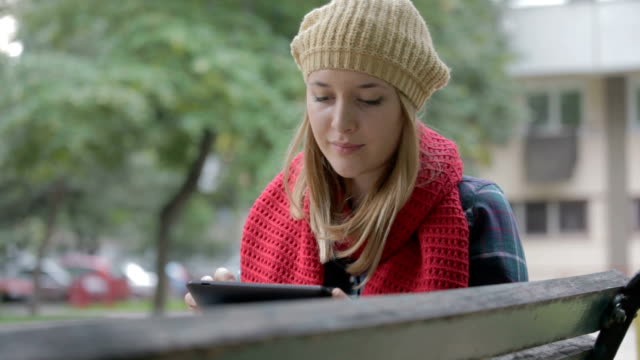 young girl with tablet pc sitting on bench outdoors - neckwear stock videos and b-roll footage