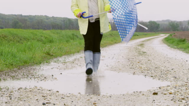 slo mo young girl with umbrella walking in a muddy puddle - one girl only videos stock videos and b-roll footage