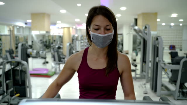 young girl  working out in gym during covid 19 pandemic,wearing face mask and rubber gloves,protection and virus spread and transfer prevention,social distancing activity rules and guidelines - thin stock videos & royalty-free footage