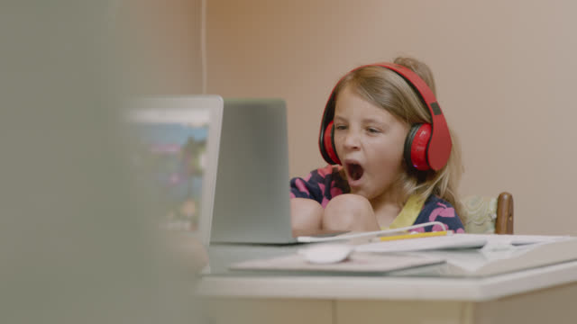 vídeos de stock, filmes e b-roll de cu of young girl yawning as she works on her online homework. - aprendizagem online