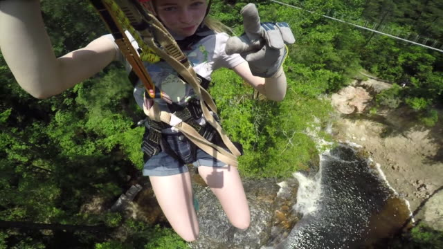 young girl zip lining over a waterfall - ロープスライダー点の映像素材/bロール