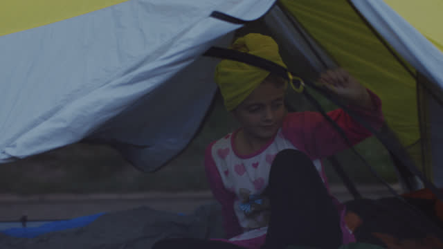 Young girl zips herself into tent and crawls into sleeping bag on family camping trip to Uncompahgre National Forest.